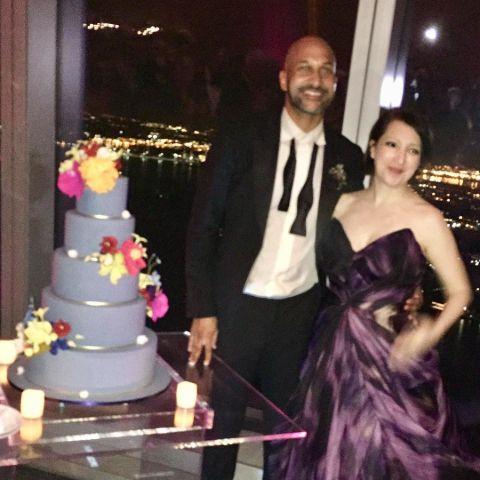 Keegan-Michael and Elisa Key standing beside their five-tier blue wedding cake.