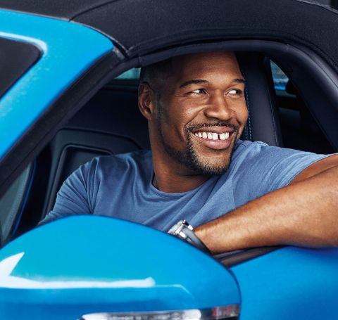 Michael Strahan looking out of his car.