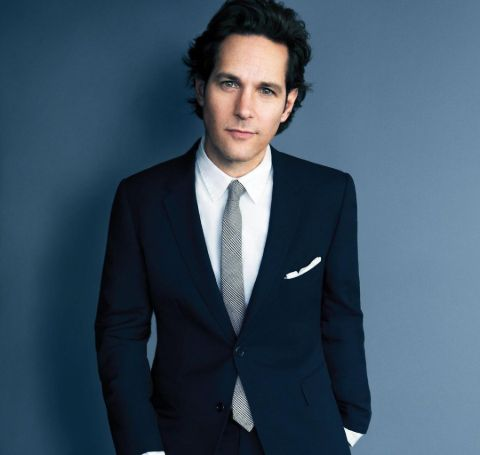 Paul Rudd wearing a black coat with white shirt and a grey tie.
