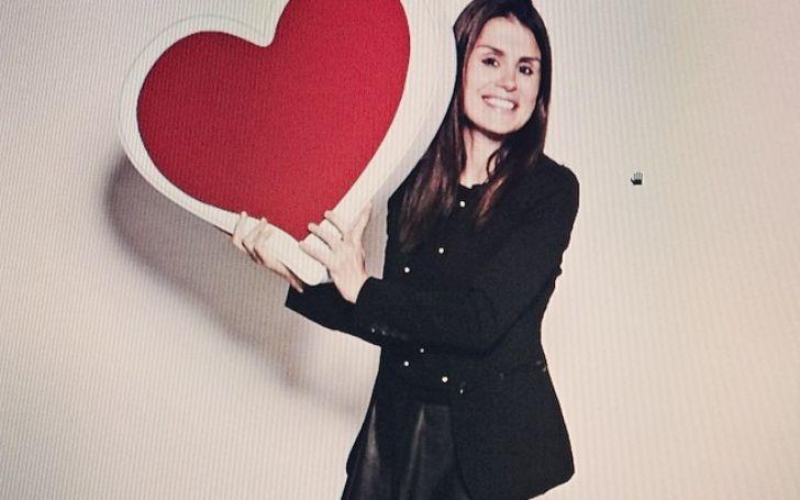 Florinka Pesenti holding a heart shaped prop.